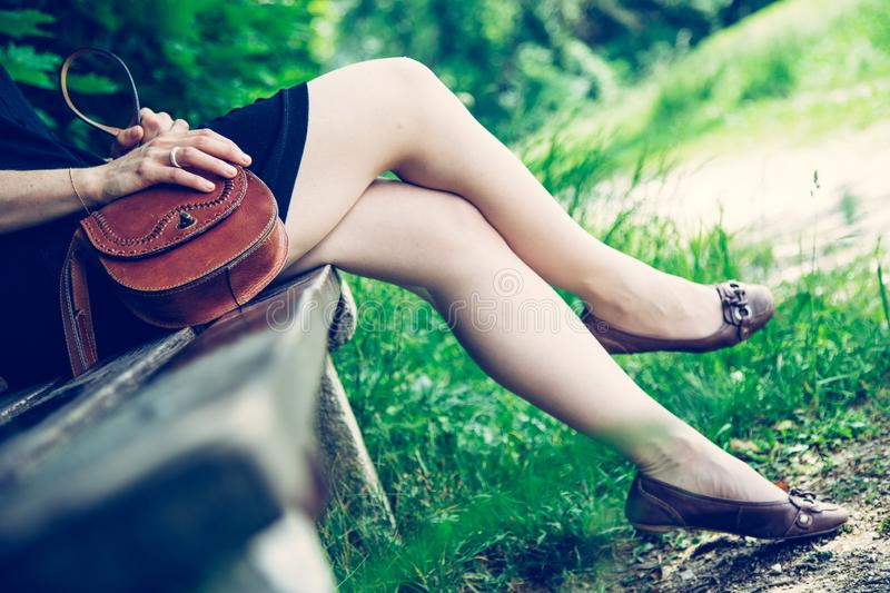 Summer in the park: Young woman in sexy black dress and ballerinas is sitting on a park bench. Young woman in black dress with sexy legs and leather handbag is royalty free stock photo