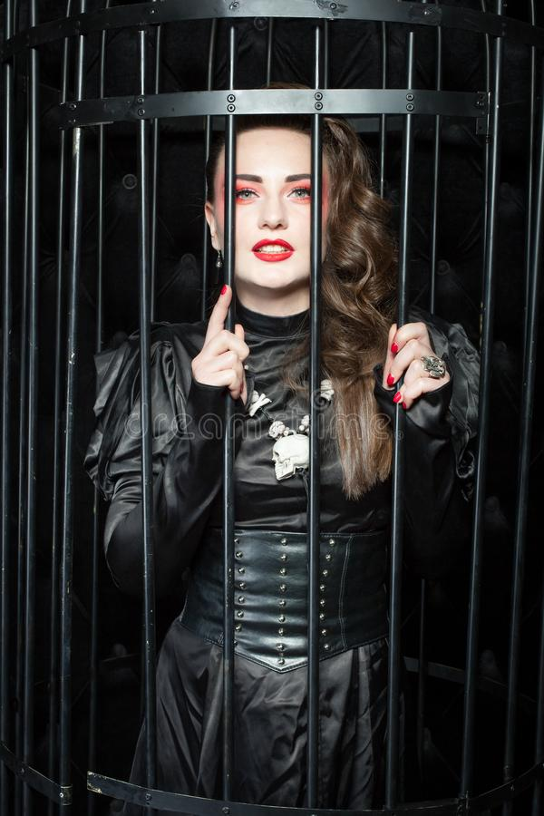 Young woman standing in a black cage. Young woman in a black dress is standing in a black cage stock image