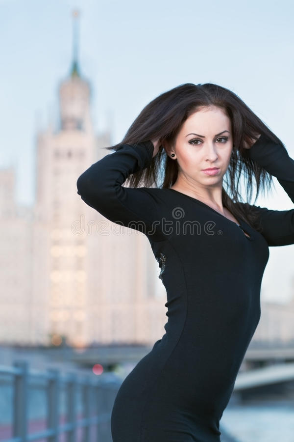Young woman in black dress standing on waterfront stock photo