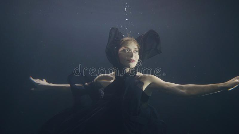 Young Woman In Black Dress Swimming Underwater On Dark