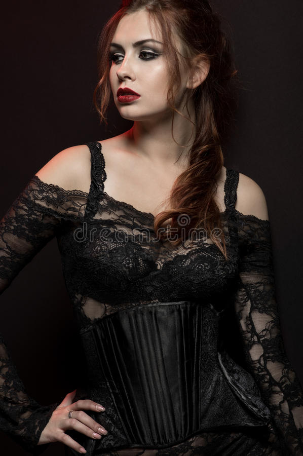 Young woman in black gothic costume. On dark background stock images