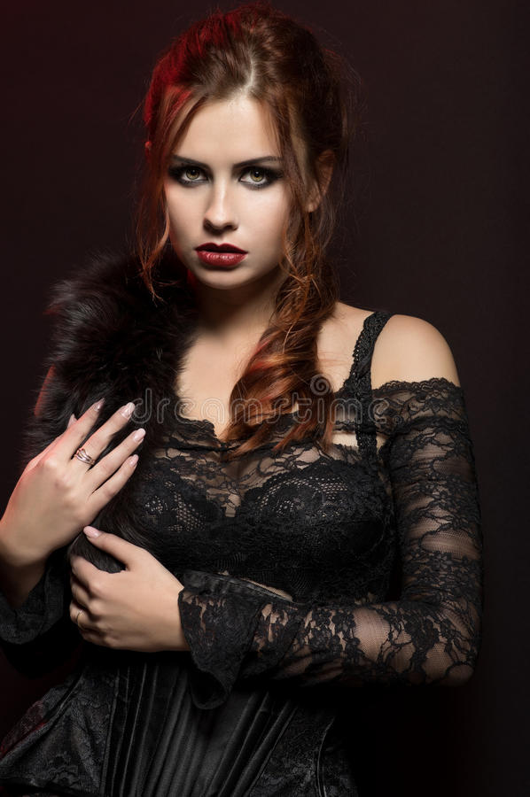 Young woman in black gothic costume. On dark background royalty free stock photography