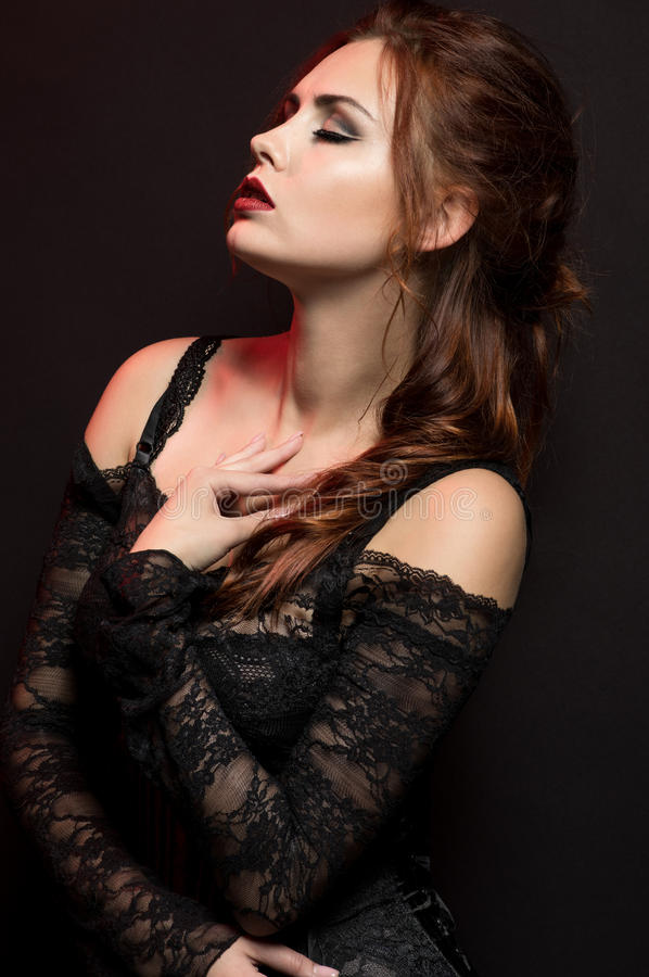 Young woman in black gothic costume. On dark background stock photography