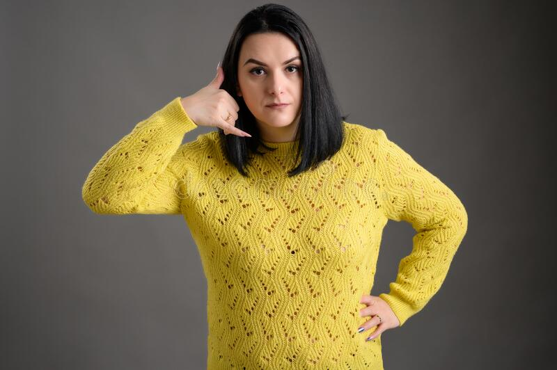 Beautiful woman dressed casually shows call me gesture. Young woman with black hair dressed casually in a yellow sweater shows call me gesture, posing an stock photo