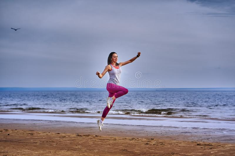 Young woman with black hair jumps while jogging. royalty free stock photo