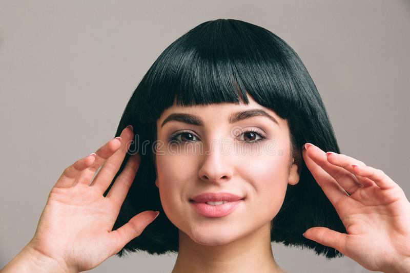 Young woman with black hair posing on camera. Attractive brunette with bob haircut. Model touching it with both hands. Isolated on light background in studio royalty free stock images