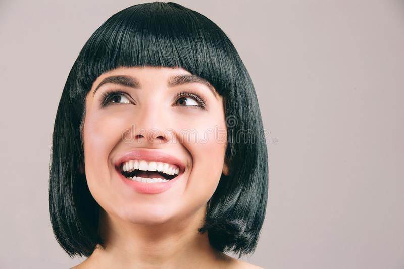 Young woman with black hair posing on camera. Brunette bob haircut. Smiling and looking up to left. Cheerful young woman. Isolated on light background stock photography