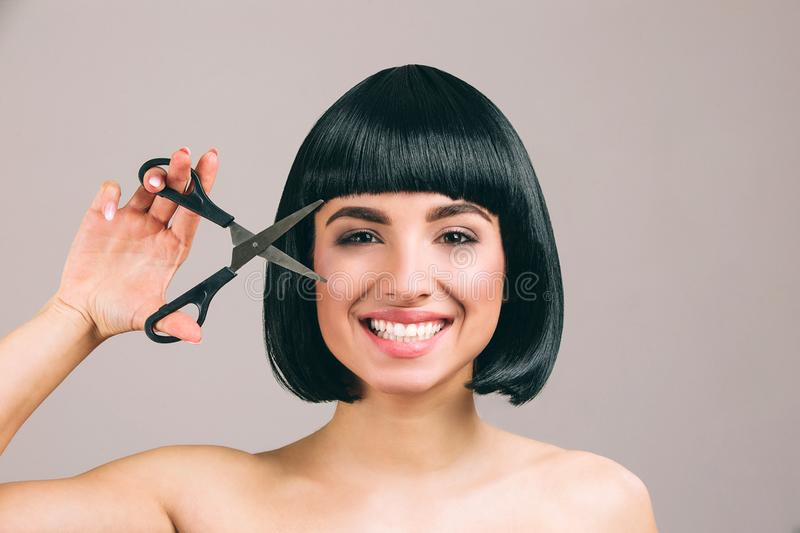 Young woman with black hair posing on camera. Cheerful nice brunette with bob haircut smiling. Looking straight through. Scissors. Isolated on light background stock photo