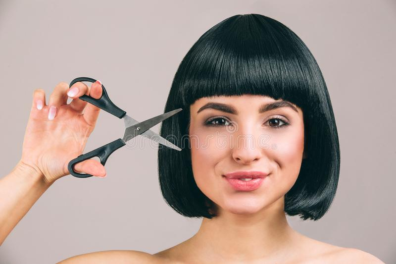 Young woman with black hair posing on camera. Cheerful nice confident brunette with bob haircut looking straight. Holding opened scissors. Isolated on light stock photo