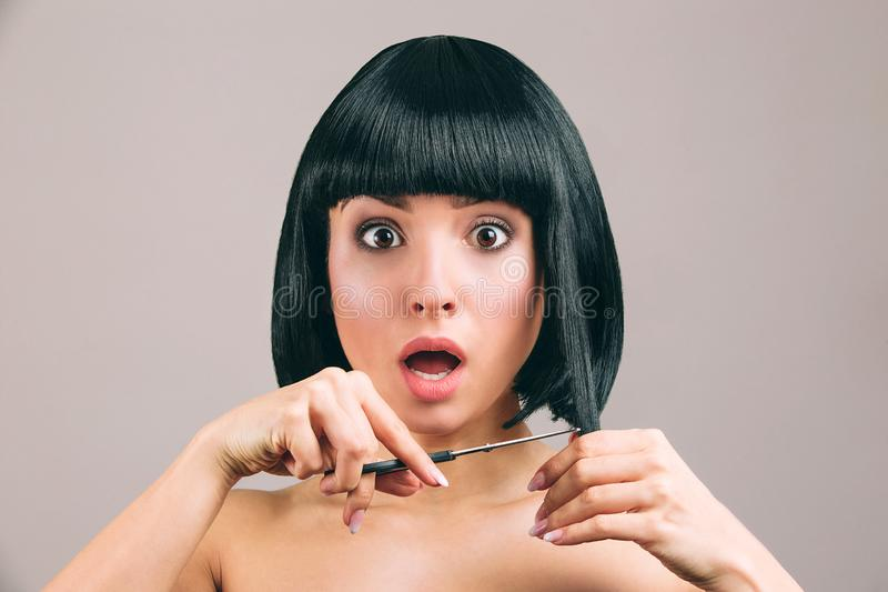 Young woman with black hair posing on camera. Cutting pieces of hair from bob haircut. Holding scissors in hand. Amazed. And scared looking on camera royalty free stock photos