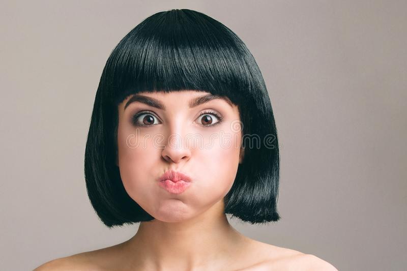 Young woman with black hair posing on camera. Expressive emotional model with bob haircut. Isolated on light background. Studio shot. Mouth full of air stock image