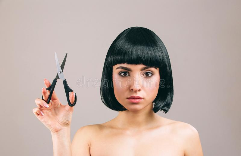 Young woman with black hair posing on camera. Looking straight. Holding scissors in hand. Serious brunette with bob. Haircut. Isolated on light background stock image