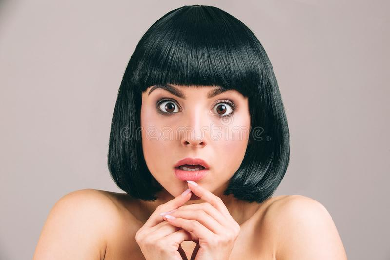 Young woman with black hair posing on camera. Scared model with bob haircut look straight. Holding fingers under lips. Isolated on light background royalty free stock photo