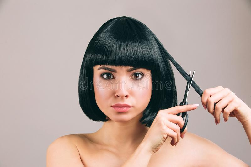 Young woman with black hair posing on camera. Serious confident brunette with bob haircut. Holding scissors and cutting. Piece of hair. Isolated on light stock photography