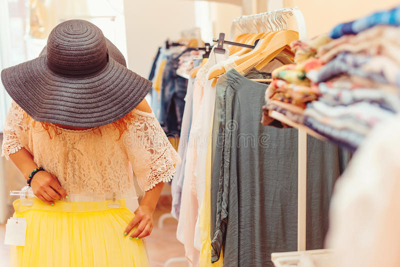 Young woman in black hat shopping in women store. Shopping time. Summer sale. Young woman in black hat shopping in woman a store. Shopping time. Summer sale stock image