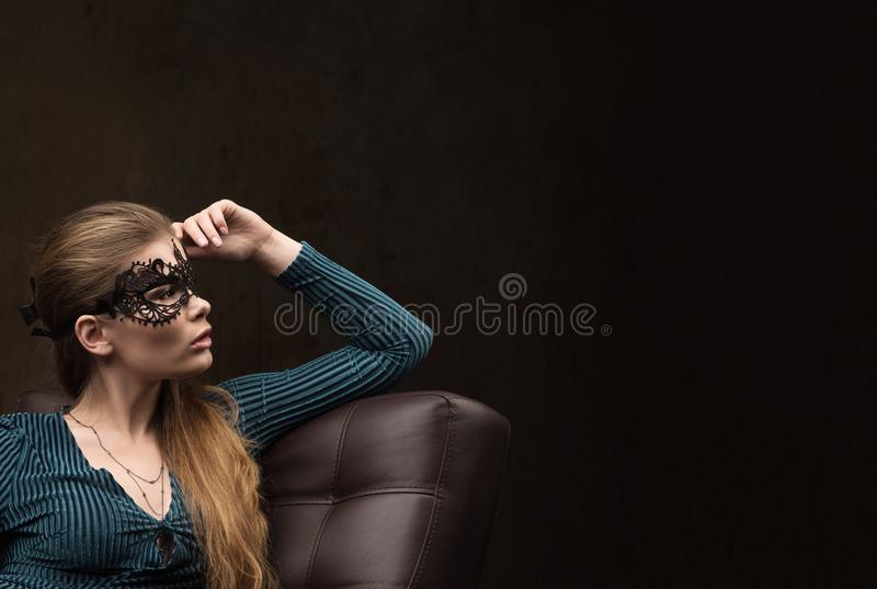 Young woman in black lace mask on the eyes looking to the side sitting on the couch stock photos