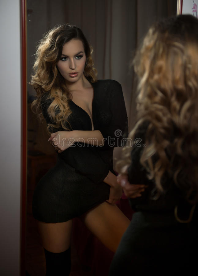 Young woman in black outfit looking into large wall mirror. Beautiful curly fair hair girl posing in front of mirror. Sensual blonde model in short black dress royalty free stock photography