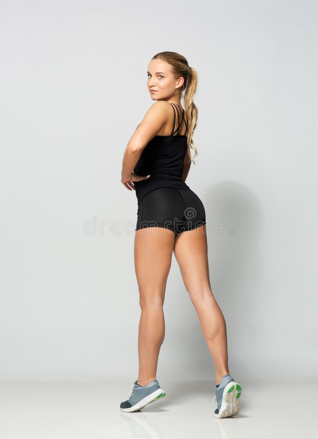 Young woman in black sportswear posing stock images