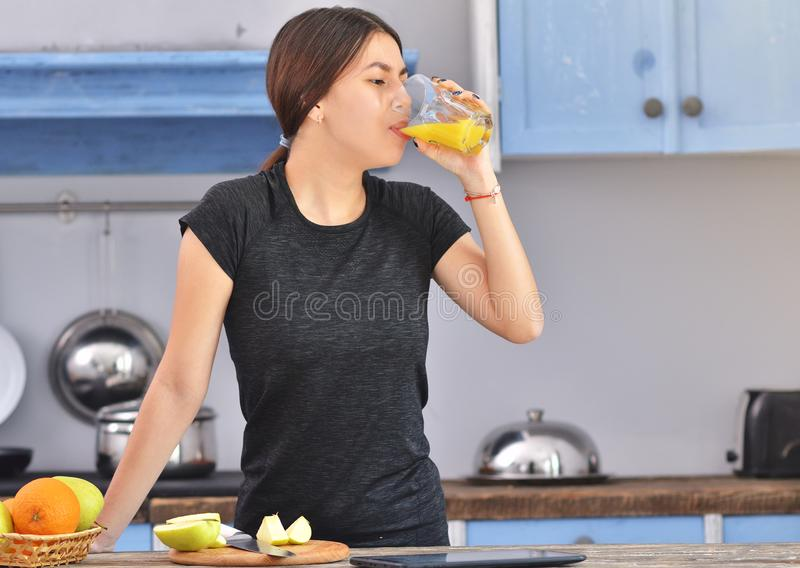 A young woman in a black t-shirt makes fit breakfast and drinks orange juice . Fruit in a bowl stands nearby. Horizontal photo, superfood, beauty, dieting stock photography