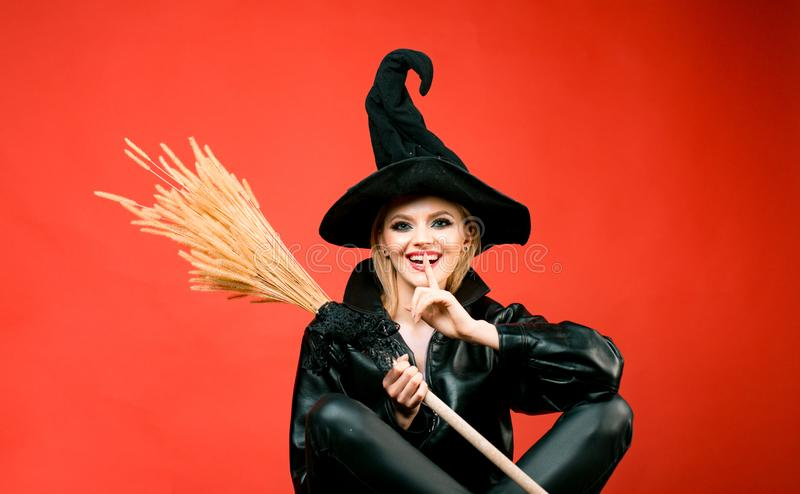Young women in black witch halloween costumes on party over red background. Witch holding broom or broomstick. stock photos
