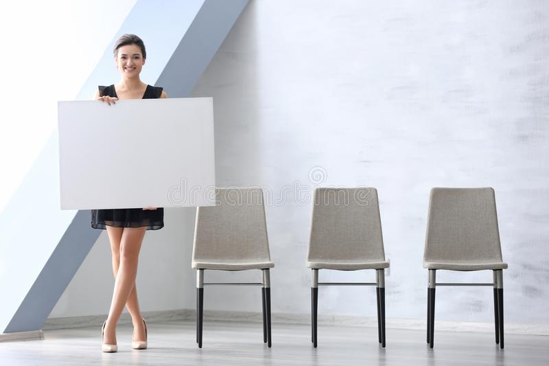 Young woman with blank advertising board stock image