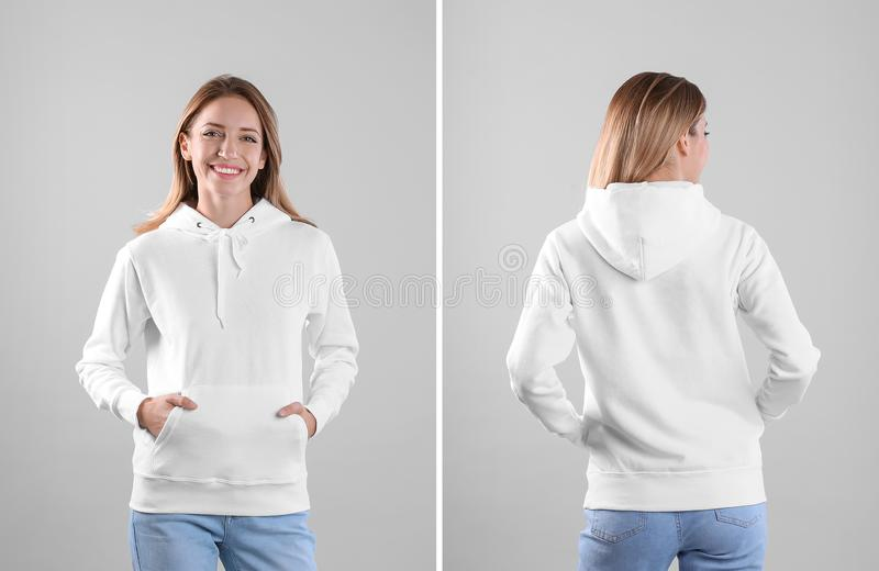 Young woman in blank hoodie sweater on light background, front and back views. royalty free stock images