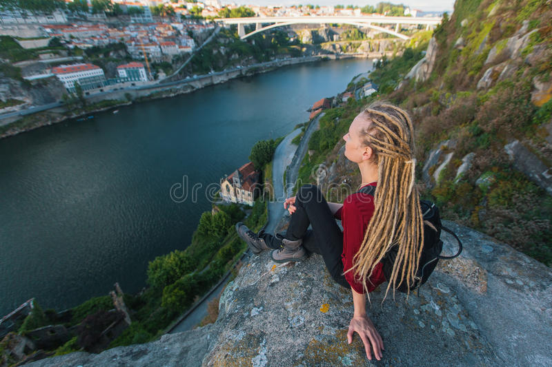Young woman with blond dreadlocks sitting on the edge of a cliff and looking at the river below. royalty free stock photos