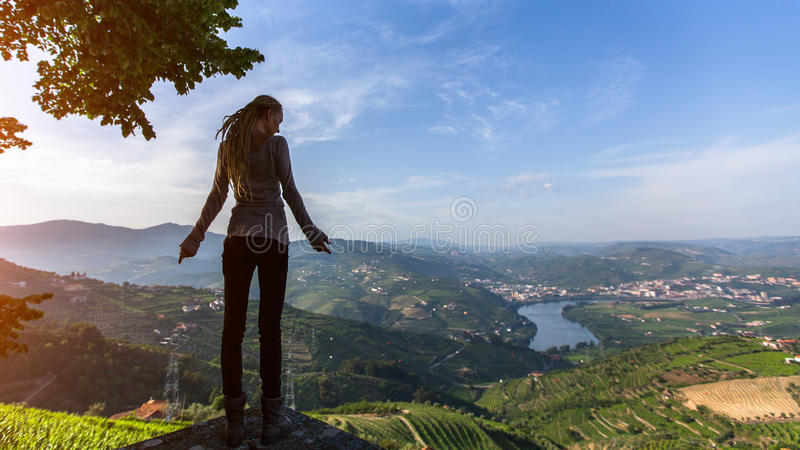 Young woman with blond dreadlocks standing on the edge of a cliff and looks down at on the Douro Valley, Portugal. Looking from the top to Vineyards on a hills stock image