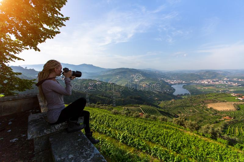 Young woman with blond dreadlocks on the viewing platform opposite Douro Valley, Portugal. Top view of river, and the vineyards are on a hills stock images