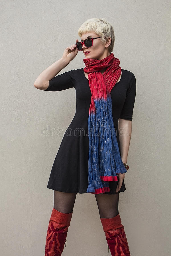 Young woman blonde in black little dress, red scarf. Fashion shot. stock photography