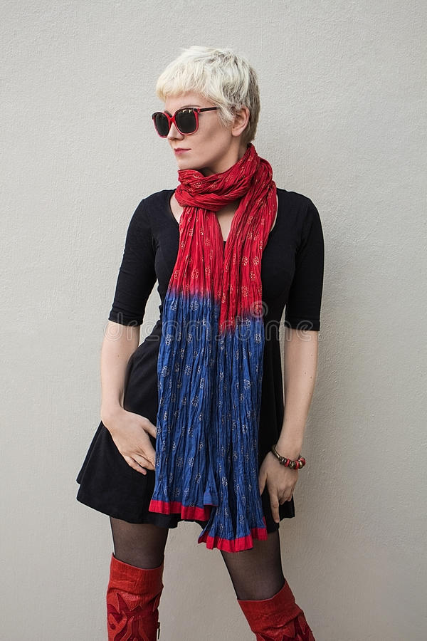 Young woman blonde in fashion black little dress, red scarf, sunglasses. royalty free stock photos