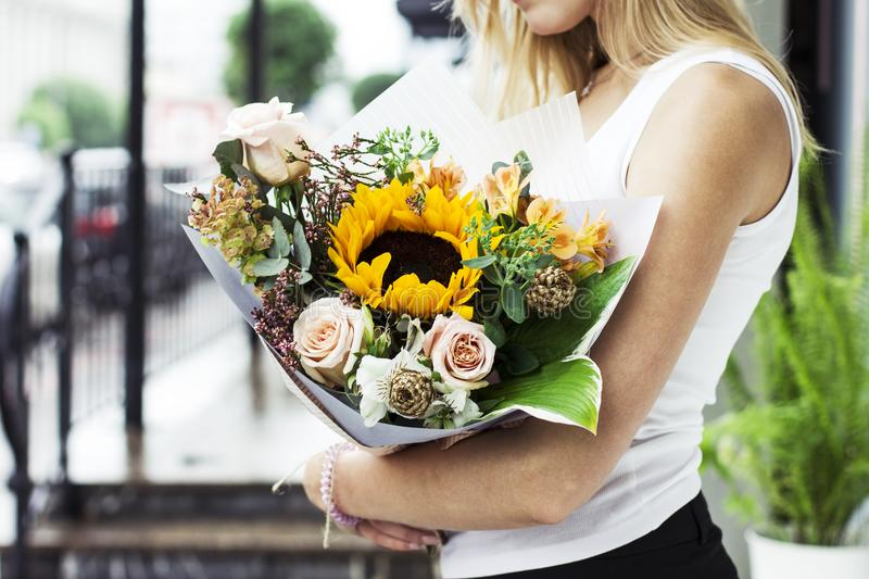 Young woman with blonde hair holding bouquet of flowers rose sunflower on street royalty free stock images