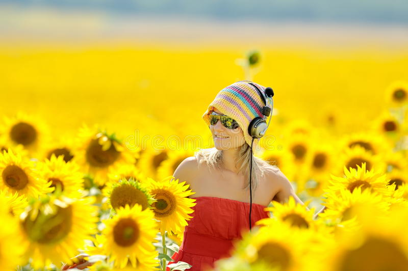 Young woman on blooming sunflower field