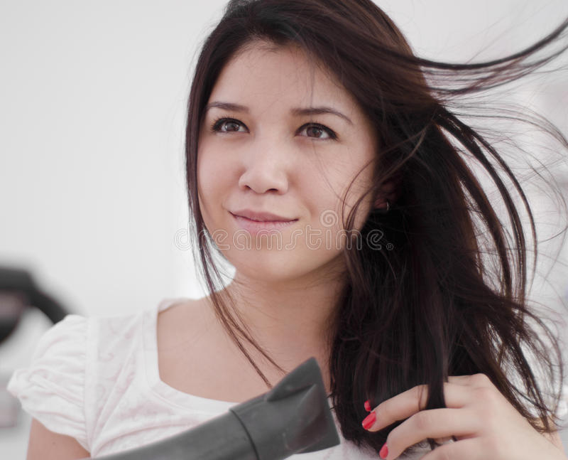 Young woman blow drying her hair. Young beautiful woman using a blow dryer and getting ready royalty free stock photo