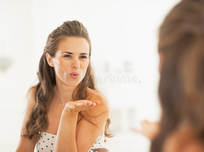 Young woman blowing air kiss in mirror stock images