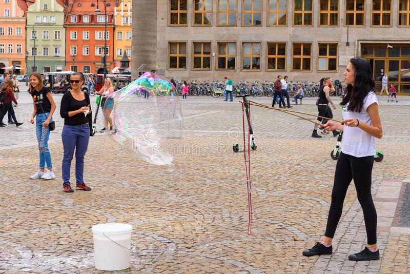 Young woman blowing bubbles on the Market Square in Wroclaw royalty free stock images