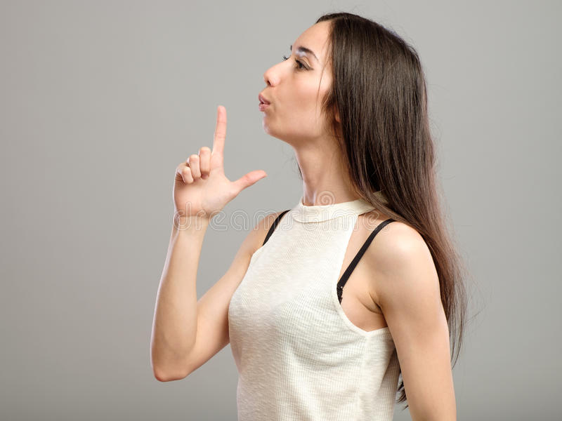 Young woman blowing on her hand gun sign. Gorgeous young woman blowing on her hand gun sign with her fingers isolated on studio background stock photo