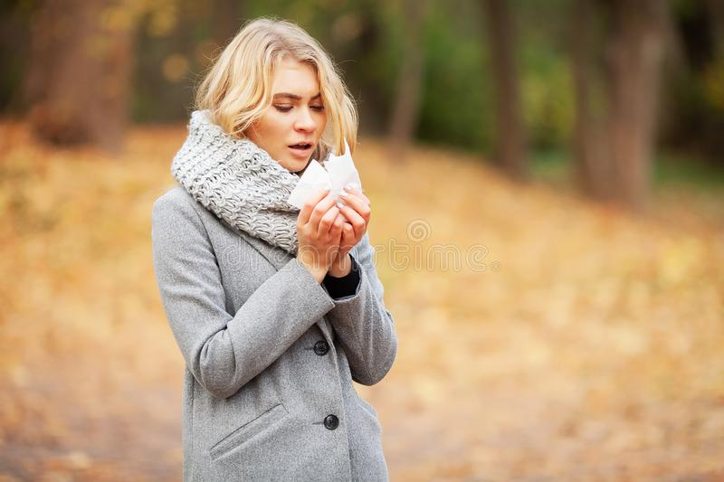 Young woman blowing her nose on the park. Woman portrait outdoor sneezing because cold and flu.  royalty free stock photos