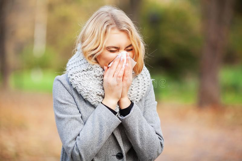 Young woman blowing her nose on the park. Woman portrait outdoor sneezing because cold and flu.  stock image