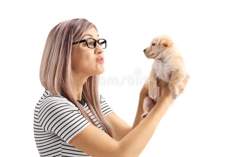 Young woman blowing a kiss to a little puppy dog stock photos
