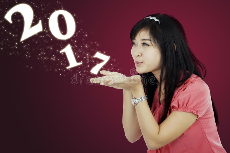Young woman blowing number 2017 stock photos