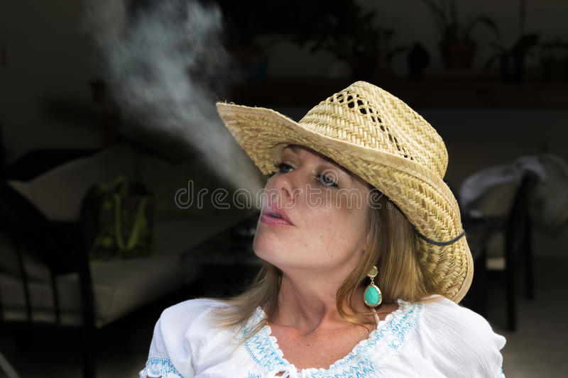 Young Woman Blowing Smoke. Photo of a young model blowing smoke royalty free stock image