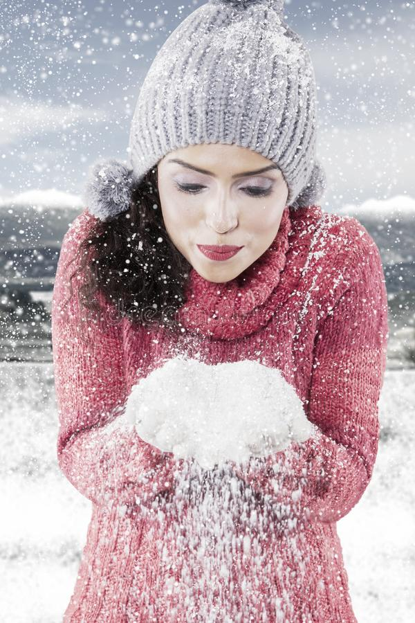 Young woman blowing snow from her hands stock images