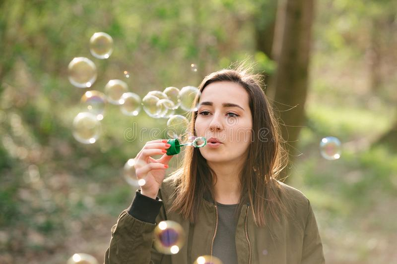 Young woman blowing soap bubbles in the woods royalty free stock photography
