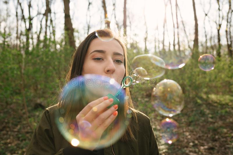 Young woman blowing soap bubbles in the woods stock photography