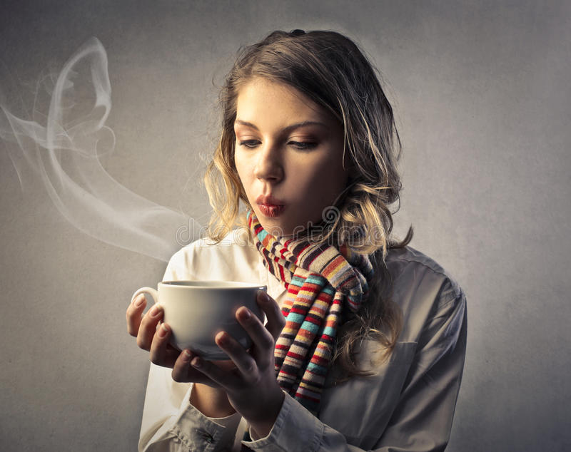 Young woman blowing on a tea cup. Young woman with a scarf blowing the steam away of a cup of tea royalty free stock photo