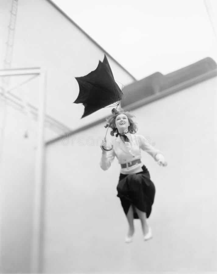 Young woman is blown away, jumping from a roof with an umbrella royalty free stock photos