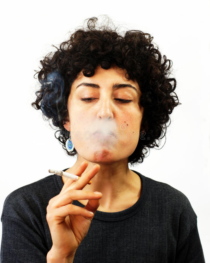 Young woman blows smoke. Young woman is holding a cigarette and blowing smoke stock photos
