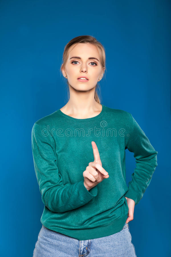 Young woman on a blue background showing signs. Pretty young woman on a blue background showing signs royalty free stock images