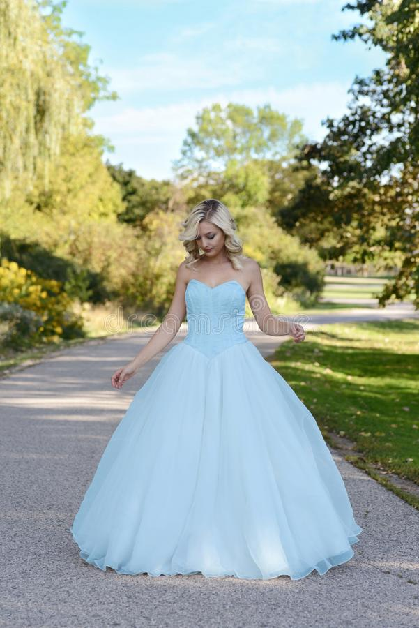 Young woman in blue ball gown in garden stock photo